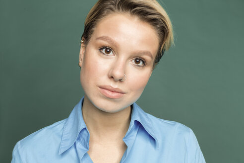 Portrait of young woman with nose piercing in front of green background - VGF00150