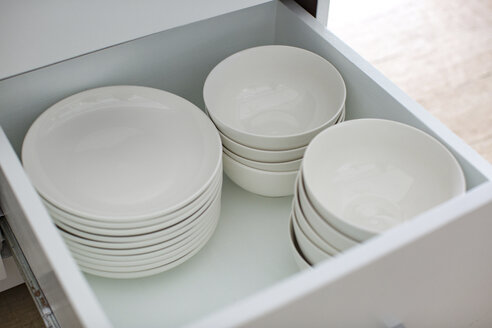 Opened drawer with white plates and bowls - MOMF00580
