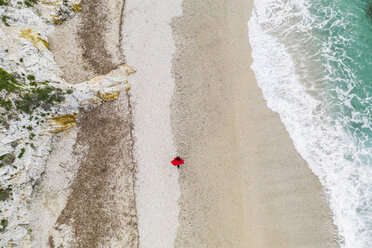Italy, Elba, woman with red coat walking at beach, aerial view with drone - FBAF00218