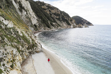 Italy, Elba, woman with red coat walking at beach, aerial view with drone - FBAF00221