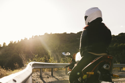 Italy, Elba Island, female motorcyclist at viewpoint - FBAF00227