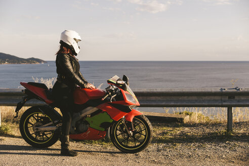 Italy, Elba Island, female motorcyclist at viewpoint - FBAF00230