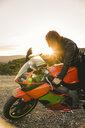 Italy, Elba Island, female motorcyclist against the sun - FBAF00233