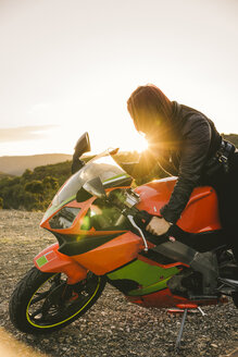 Italy, Elba Island, female motorcyclist against the sun - FBAF00233