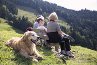 Austria, Tyrol, Kaiser mountains, hikers with dog resting on a bench in the mountains - MAMF00275