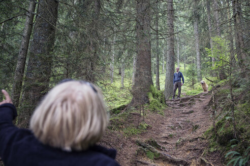 Austria, Tyrol, Kaiser mountains, mother and adult son with dog hiking in forest - MAMF00278