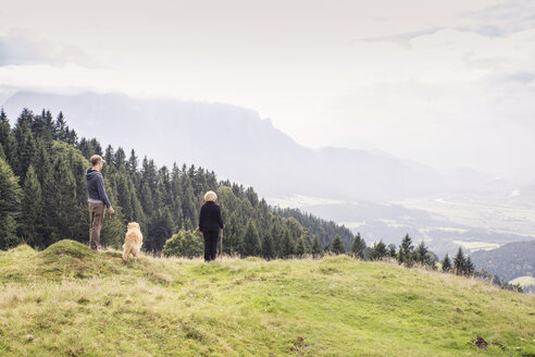 Austria, Tyrol, Kaiser mountains, mother and adult son with dog on a hiking trip in the mountains - MAMF00281