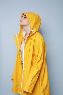 Young woman wearing yellow rain coat in front of blue background - GRSF00047