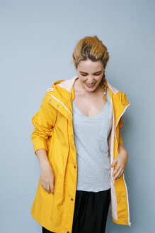 Laughing young woman wearing yellow rain coat in front of blue background - GRSF00050