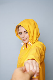 Portrait of smiling young woman wearing yellow rain coat in front of blue background holding hands - GRSF00053