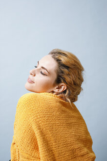 Smiling young woman wearing yellow knitwear in front of blue background - GRSF00056