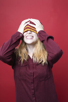 Grinning young woman wearing wooly hat in front of red background - GRSF00059