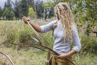 Archeress sorting bow and arrows in nature - TCF06065