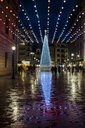 Spain, Gijon, lighted Christmas tree at pedestrian area on a rainy day in the evening - MGOF03924