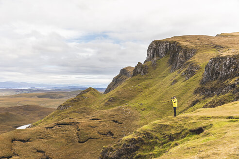 UK, Scotland, Isle of Skye, Quiraing, photographer on top of a cliff taking photos - WPEF01230