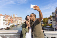 Italy, Venice, happy young couple on a bridge taking a selfie - WPEF01233