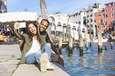 Italy, Venice, playful couple relaxing and taking a selfie with Rialto bridge in background - WPEF01242