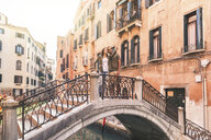 Italy, Venice, young couple standing on a small bridge exploring the city - WPEF01248