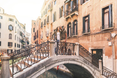 Italy, Venice, couple over a small bridge, enjoying a visit to the city - WPEF01248
