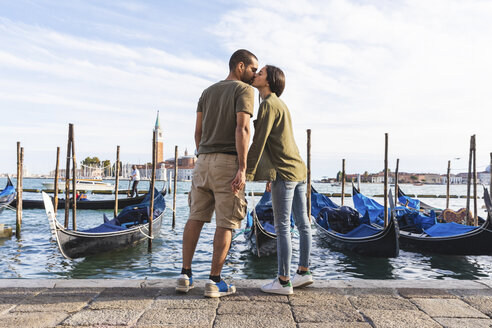 Italy, Venice, affectionate young couple kissing with gondola boats in background - WPEF01251