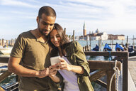 Italy, Venice, affectionate young couple with cell phone and gondola boats in background - WPEF01254