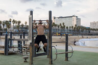 Barechested muscular man doing chin-ups on the beach - MAUF02217