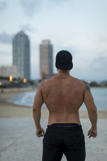 Rear view of barechested muscular man on the beach at dusk - MAUF02232
