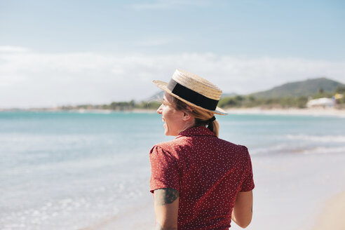 Spain, Mallorca, back view of happy   young woman with tattoos on the beach - LOTF00014