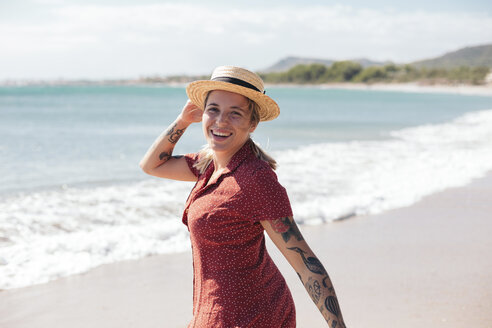 Spain, Mallorca, portrait of happy young woman with tattoos on the beach - LOTF00017