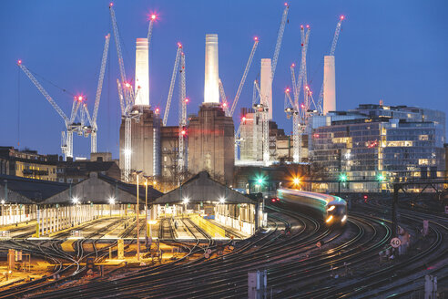 United Kingdom, England, London, view of railtracks and trains in the evening, former Battersea Power Station and cranes in the background - WPEF01265