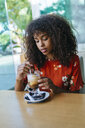 Portrait of young woman drinking  coffee in a cafe - KIJF02135