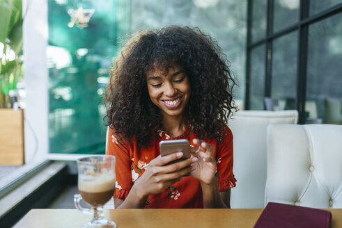 Portrait of smiling young woman in coffee shop using cell phone - KIJF02138