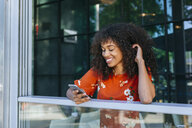 Smiling young woman leaning on window sill of a coffee shop looking at cell phone - KIJF02147