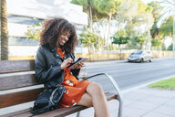 Happy young woman sitting on a bench using digital tablet - KIJF02162