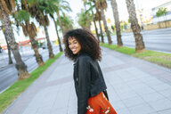 Portrait of happy young woman on promenade - KIJF02165