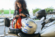 Smiling young woman removing safety lock from her motorcycle - KIJF02171