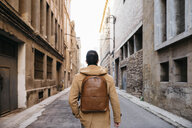 Spain, Igualada, rear view of man with backpack walking through the industrial zone of the town - JRFF02291