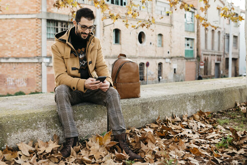 Spain, Igualada, smiling man sitting down using cell phone in the autumnal town - JRFF02294