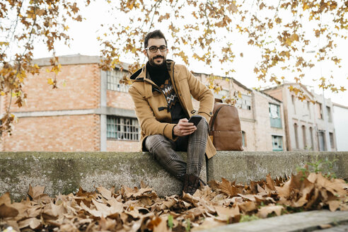 Spain, Igualada, portrait of smiling man with cell phone sitting down in the autumnal town - JRFF02297