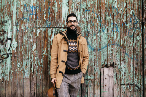 Spain, Igualada, portrait of smiling man standing at rundown wooden gate - JRFF02303