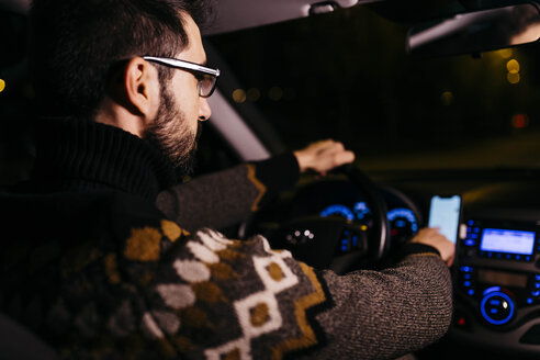 Man using cell phone with road maps in the car at night - JRFF02321