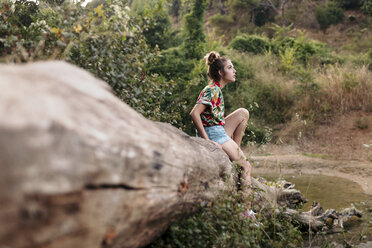 Young woman sitting on a trunk surrounded by nature - LOTF00023