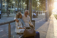 Spain, Barcelona, senior couple with baggage sitting at tram stop in the city at sunset - MAUF02237