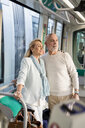 Senior couple standing in a tram looking around - MAUF02243