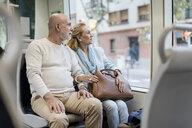 Senior couple sitting in a tram - MAUF02246