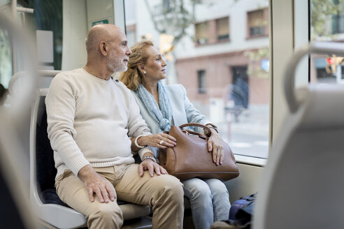 Senior couple sitting in a tram - MAUF02246