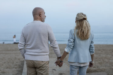 Spain, Barcelona, rear view of senior couple walking hand in hand on the beach at dusk - MAUF02255