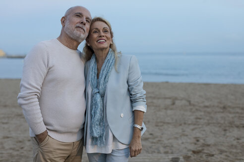 Spain, Barcelona, happy senior couple on the beach at dusk - MAUF02258