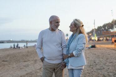Spain, Barcelona, happy senior couple on the beach at dusk - MAUF02264