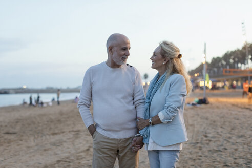 Spain, Barcelona, happy senior couple on the beach at dusk - MAUF02264